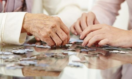 Senior Citizen Hands - solving a jigsaw puzzle